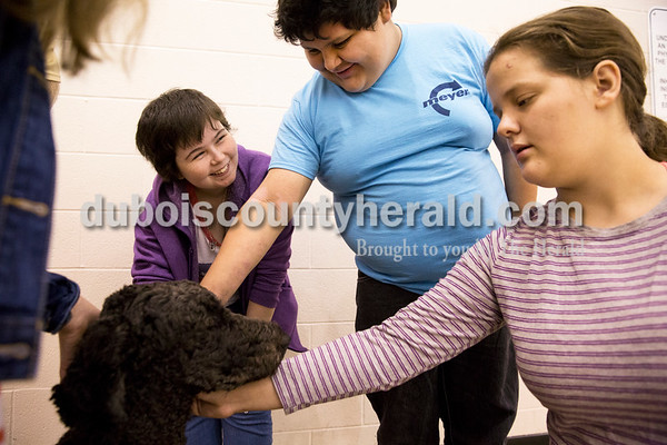 Sarah Ann Jump/The Herald Jasper High School junior Shania Scarbrough, left, sophomore Kaleb Lopez and freshman Kimberly Gentry pet Dexter, a comfort dog owned by teacher Nick Eckert, at the school on Friday morning.