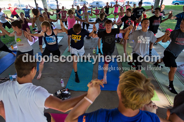 Members of the Southridge High School football team participated in Yes Power Yoga's free yoga class led by owner Erin Rauscher during Herbstfest on Saturday in Huntingburg.  Alisha Jucevic/The Herald