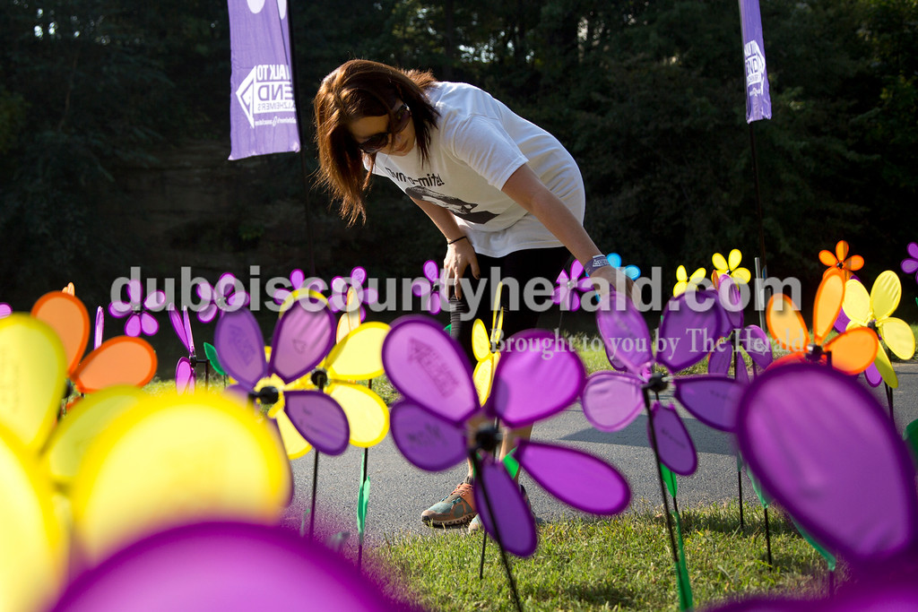 "Sarah Shaw/The Herald<br /> Nicole McClain of Huntingburg read the messages on the flowers in the Promise Garden during the Walk to End Alzheimer's at the Jasper Riverwalk on Saturday. Participants ""planted"" flowers honoring and remembering those affected by the disease. This year's event raised over $53,000 for the Alzheimer's Association, which helps fund Alzheimer's support, care, and research."