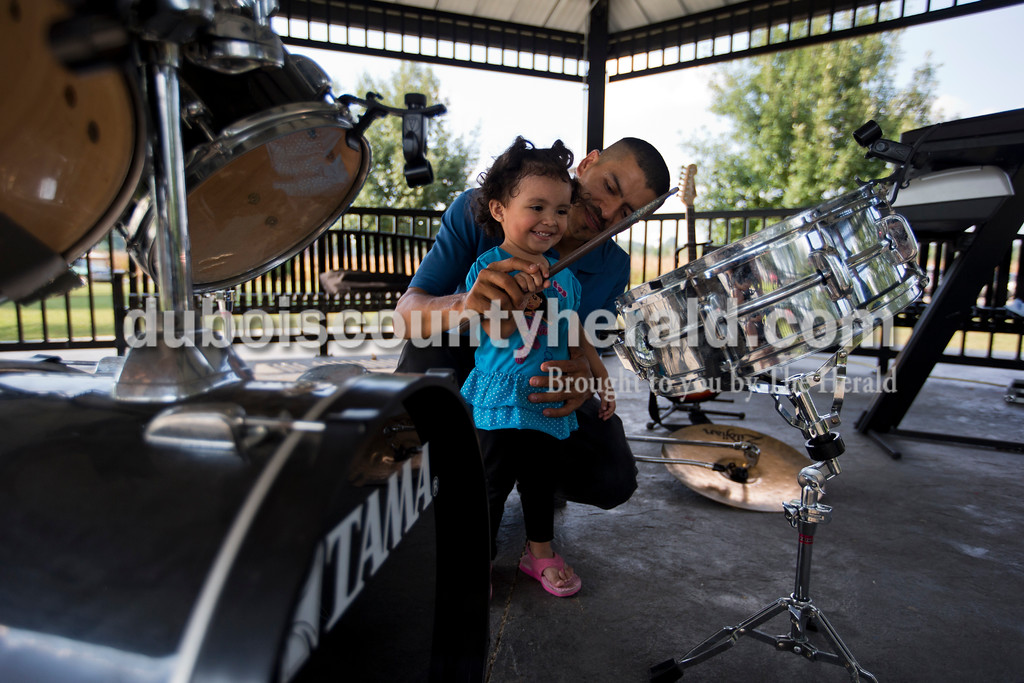 Bertilio Dubon and his daughter Sofia, 2, both of Huntingburg, played on a drum set as Bertilio and his bandmates from The Los Guanacos Band broke down their instruments after a performance during Herbstfest on Saturday in Huntingburg. <br /> Alisha Jucevic/The Herald