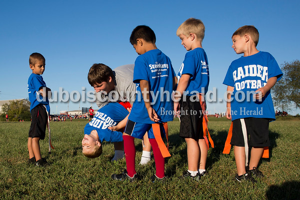 Sarah Ann Jump/The Herald Coach Sam White of Huntingburg, 17, tipped over Bryson Childree, 5, as his flag football teammates Jaxin McCormick, 5, left, Ricardo Vanegas, 5, Riley Messmer, 5, and Mason Bayer, 5, all of Huntingburg, watched during a practice at Southridge High School in Huntingburg on Monday. Seniors on the Southridge High School football team coach the flag football league for kindergarten, first and second grade students in Huntingburg and Holland.