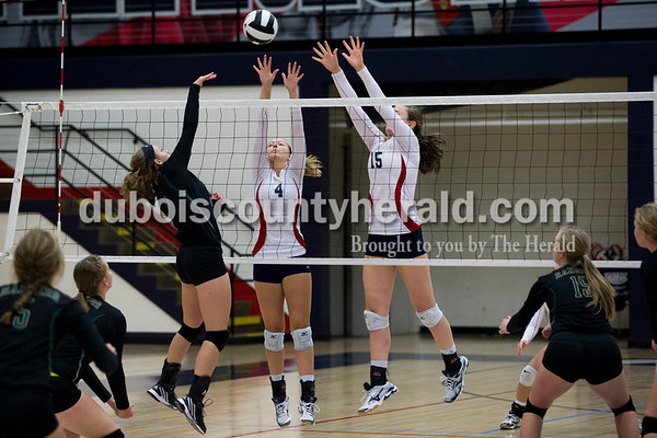 Forest Park's Clarissa Weyer spiked the ball over the net as Heritage Hills' Abby Wetzel and Abby Wahl jumped up to block during Monday night's game in Lincoln City. The Patriots won 25-11, 25-13, 25-8.  Alisha Jucevic/The Herald