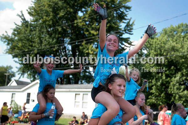 Jillian Bailey of Winslow, 11, carried Danica Taylor of Huntingburg, 10, on her shoulders as they walked along with the Flip and Twist float  during the Herbstfest parade on Sunday afternoon in Huntingburg.  Alisha Jucevic/The Herald