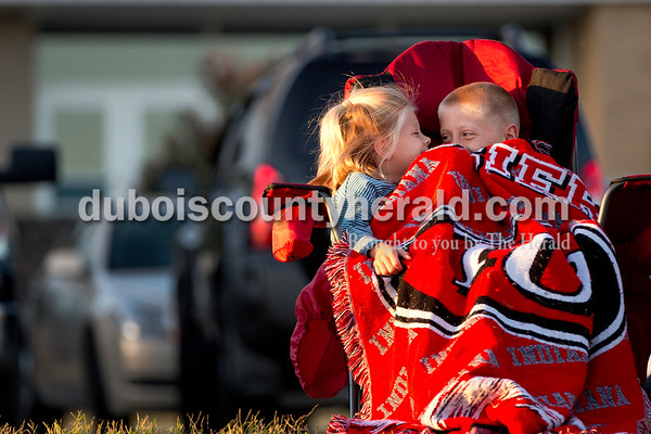 Grace Dooley of Dubois, 7, and her brother Adam, 9, shared a blanket while watching the game in Dubois on Tuesday. Heritage Hills won 3-0.  Sarah Shaw/The Herald