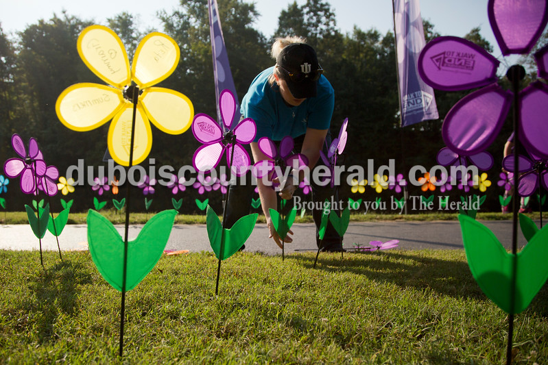 "Sarah Shaw/The Herald<br /> Wendy Broughton of Santa Claus helped plant flowers in honor of those affected by Alzheimer's during the Walk to End Alzheimer's at the Jasper Riverwalk on Saturday. Participants ""planted"" flowers honoring and remembering those affected by the disease. This year's event raised over $53,000 for the Alzheimer's Association, which helps fund Alzheimer's support, care, and research."