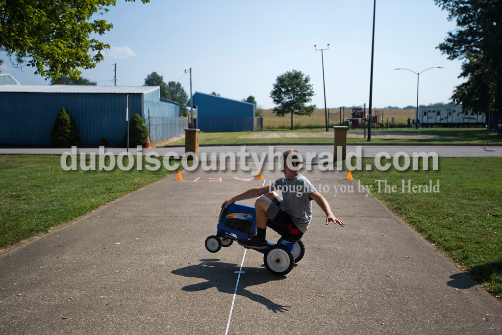Trevor Hunefeld of Holland, 14, goofed around on a pedal tractor before the Kiddie Pedal Pull during Herbstfest on Saturday in Huntingburg. <br /> Alisha Jucevic/The Herald