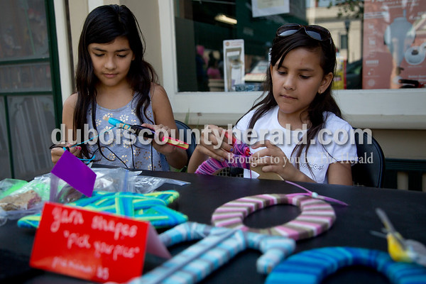 Sarah Shaw/The Herald Eliana Ortega of Jasper, 10, and her sister Josefina, 8, made yarn shapes during the 21st annual Kids Day held by the Greater Downtown Jasper Business Association on the square in Jasper on Saturday. Children in grades Kindergarten – 12th grade had the opportunity to set up booth around the square to buy, sell, or trade their goods.