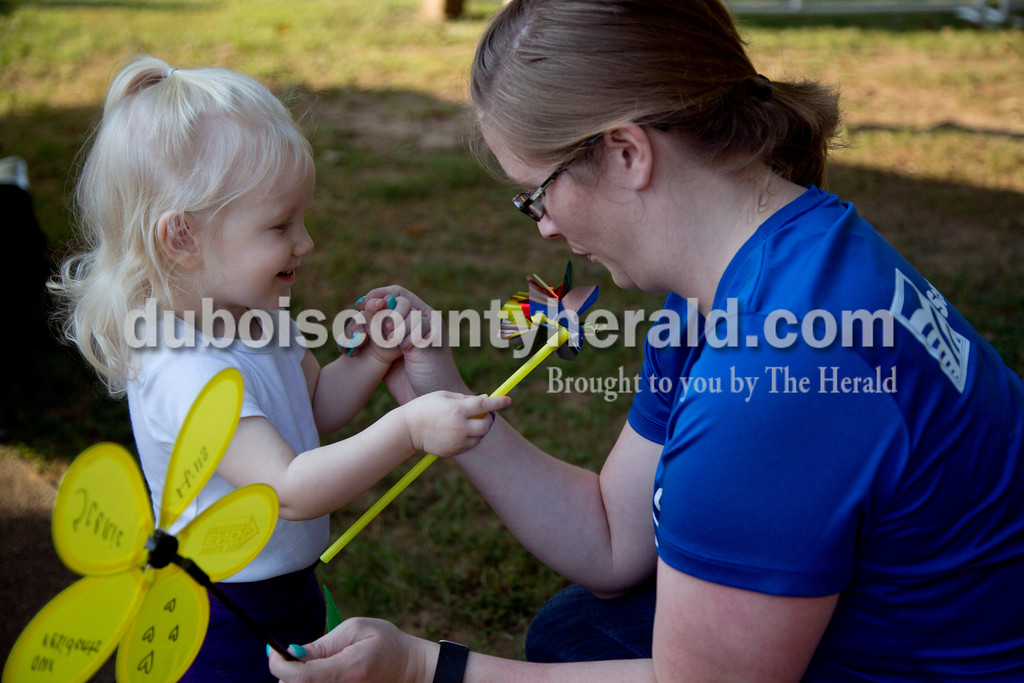 "Sarah Shaw/The Herald<br /> Presley Leinenbach of Holland, 1, held a pinwheel for her mother, Audrey to blow before the start of the Walk to End Alzheimer's at the Jasper Riverwalk on Saturday. Participants ""planted"" flowers honoring and remembering those affected by the disease. This year's event raised over $53,000 for the Alzheimer's Association, which helps fund Alzheimer's support, care, and research."