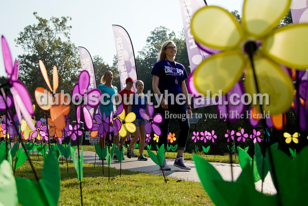 "Sarah Shaw/The Herald<br /> Jessi Luegers of Jasper walked through Promise Garden during the Walk to End Alzheimer's at the Jasper Riverwalk on Saturday. Participants ""planted"" flowers honoring and remembering those affected by the disease. This year's event raised over $50,000 for the Alzheimer's Association, which helps fund Alzheimer's support, care, and research."