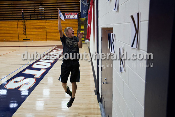 """Heritage Hills High School junior Austin Schnuck jumped in the air to slap a laminated """"K"""" onto the wall during Monday night's game against Forest Park in Lincoln City. The student section applied tape to 50 laminated sheets of paper with """"K"""" written on them, and added a new one to the wall each time the Patriots got a kill shot. The Patriots won 25-11, 25-13, 25-8.  Alisha Jucevic/The Herald"""