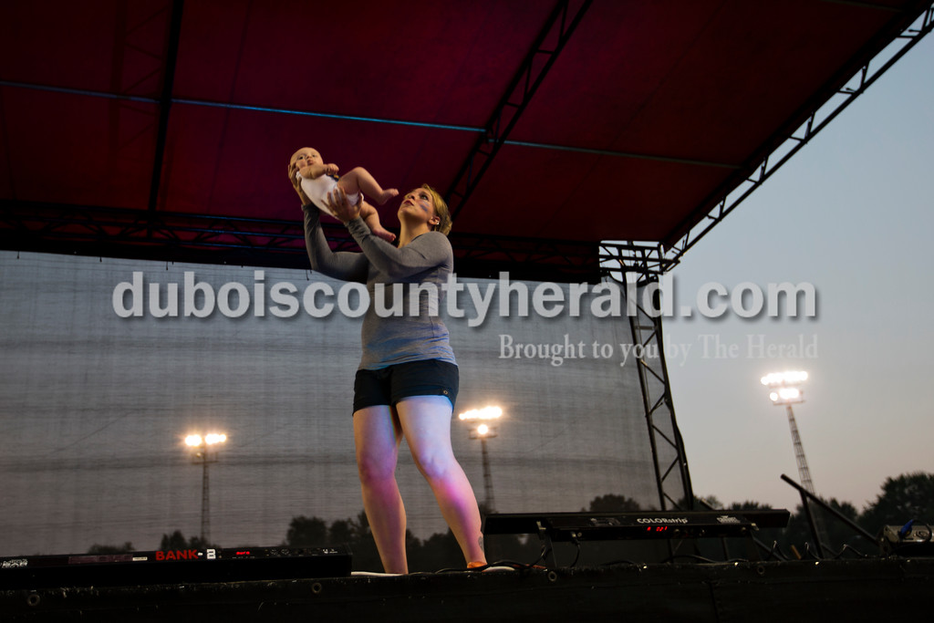 "Emily Meyer of Huntingburg held up her three-month-old baby Wade during her rendition of ""Circle of Life"" in her lip-sync battle against her twin Elizabeth Wertman during Herbstfest on Saturday in Huntingburg. The twins started performing in Puttin' on the Hits in fifth grade, and years later, in 2013, they became chairman and organizers for the event.  <br /> Alisha Jucevic/The Herald"