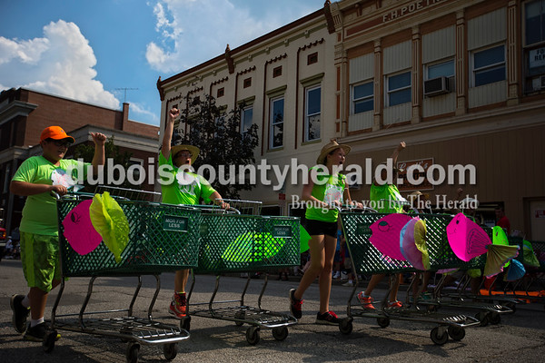 Pushing Mor for Less shopping carts, the Shared Abundance float collected canned goods and other items throughout the Herbstfest parade on Sunday afternoon in Huntingburg.  Alisha Jucevic/The Herald
