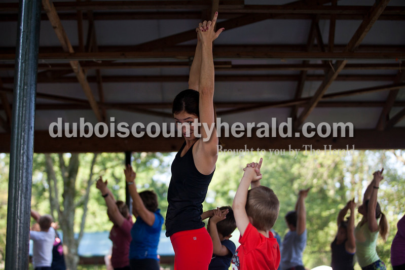 Kelsey Menke of Huntingburg, encouraged her son, Will, 4, during a free Yes Power Yoga class at Herbstfest on Saturday morning in Huntingburg City Park. <br /> Alisha Jucevic/The Herald