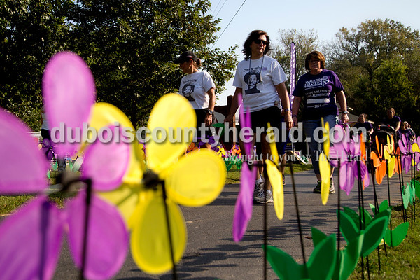 """Sarah Shaw/The Herald Mary Uebelhor of Huntingburg, center, walked through the Promise Garden during the Walk to End Alzheimer's at the Jasper Riverwalk on Saturday. Participants """"planted"""" flowers honoring and remembering those affected by the disease. Uebelhor lost her mother to the disease two months ago. This year's event raised over $53,000 for the Alzheimer's Association, which helps fund Alzheimer's support, care, and research."""
