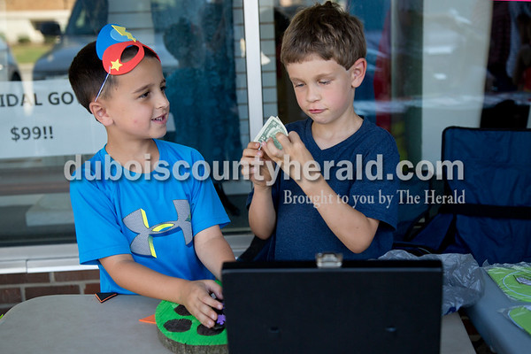 """Sarah Shaw/The Herald Mason Bower and Camden Graman, both 7 and of Jasper, inspected a $2 bill they received while selling Halloween masks during the 21st annual Kids Day held by the Greater Downtown Jasper Business Association on the square in Jasper on Saturday. """"I'm never spending this!"""" Camden said. Children in grades Kindergarten – 12th grade had the opportunity to set up booth around the square to buy, sell, or trade their goods."""
