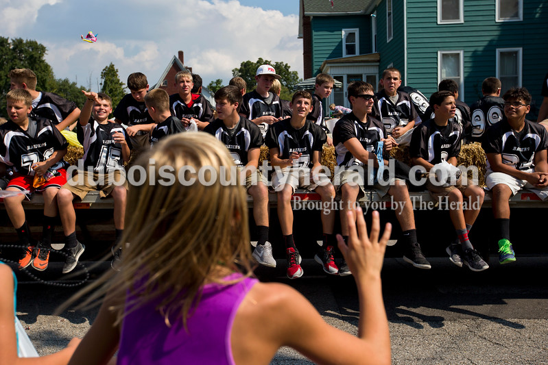 Kelsey Wibbeler of Huntingburg, 10, reached up as the Southridge Middle School football players threw candy to the crowd during the Herbstfest parade on Sunday afternoon in Huntingburg. <br /> Alisha Jucevic/The Herald