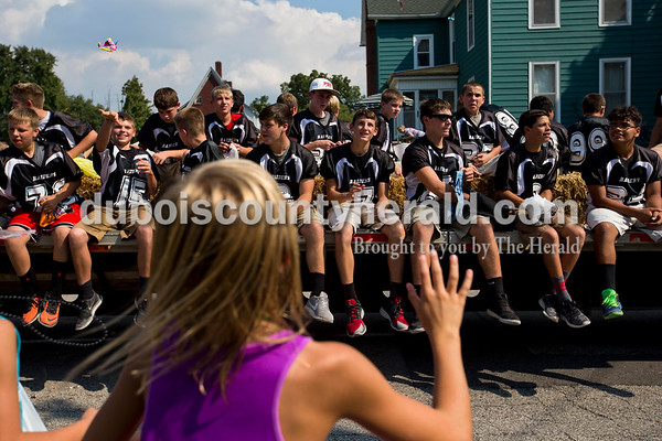 Kelsey Wibbeler of Huntingburg, 10, reached up as the Southridge Middle School football players threw candy to the crowd during the Herbstfest parade on Sunday afternoon in Huntingburg.  Alisha Jucevic/The Herald