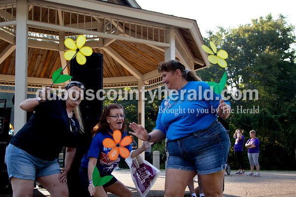 """Sarah Shaw/The Herald Bettina Gerber of Winslow, Tammy Love of Washington, and Karen Hotz of Loogootee danced before the start of the Walk to End Alzheimer's at the Jasper Riverwalk on Saturday. Participants """"planted"""" flowers in the Promise Garden honoring and remembering those affected by the disease. This year's event raised over $53,000 for the Alzheimer's Association, which helps fund Alzheimer's support, care, and research."""