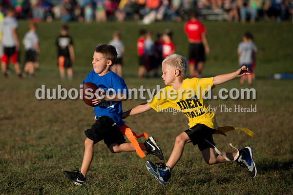 Sarah Ann Jump/The Herald Mason Bayer of Huntingburg, 5, ran with the football as Nolan Byrd of Huntingburg, 5, chased him and tried to grab his flag during Southridge Raider flag football at the school in Huntingburg on Monday. Mason succeeded in scoring a touchdown.