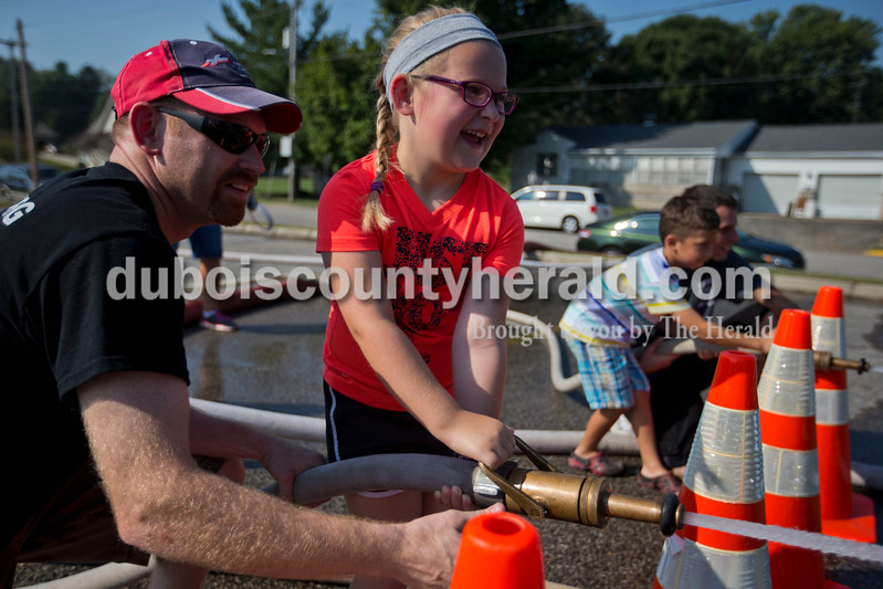 The Huntingburg Fire Department set up firefighter-themed kids games throughout the Huntingburg City Park entrance on Saturday morning. Huntingburg firefighter Chris Lee helped Addison Weyerbacher of Huntingburg, 6, play a fire hose game during during the event <br /> Alisha Jucevic/The Herald