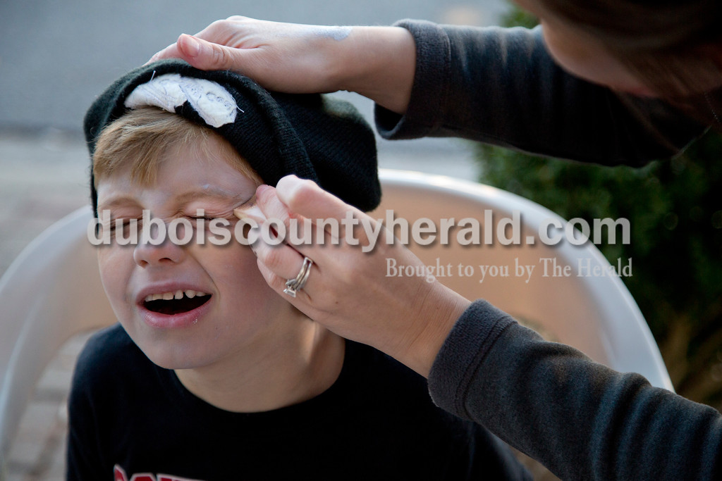 Sarah Shaw/The Herald<br /> Deacon Schwinghammer of Huntingburg, 6, had his face painted by his aunt Natasha Hall of Jasper to make him look like a zombie before the start of the Haunted Huntingburg Zombie 5K at Old Town Hall in Huntingburg on Saturday.