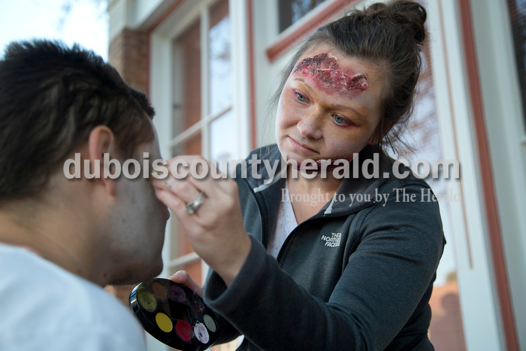 Sarah Shaw/The Herald<br /> Natasha Hall of Jasper painted the face of Brandon Weyer of Ferdinand, to make him look like a zombie before the start of the Haunted Huntingburg Zombie 5K at Old Town Hall in Huntingburg on Saturday.