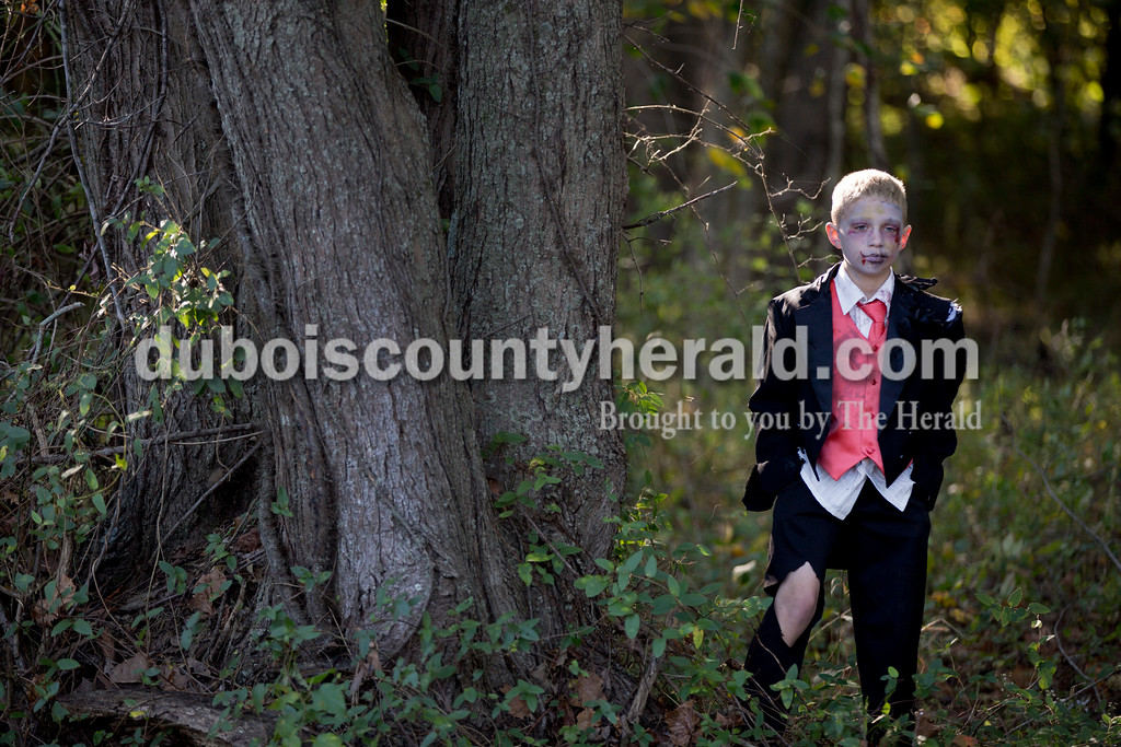 Sarah Shaw/The Herald<br /> Dressed like a zombie, Grady Siddons of Huntingburg, 8, hid behind a tree while waiting to scare runners during the Haunted Huntingburg Zombie 5K at Niehaus Park in Huntingburg on Saturday.