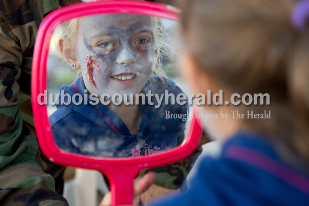 Sarah Shaw/The Herald<br /> Sophia Dilger of Mariah Hill, 7, inspected her zombie makeup before the start of the Haunted Huntingburg Zombie 5K outside the Old Town Hall in Huntingburg on Saturday.
