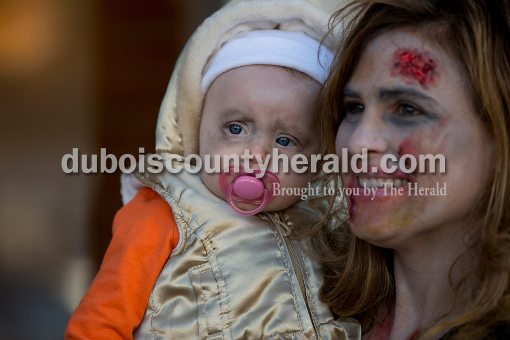 Sarah Shaw/The Herald<br /> Ginger Rasche of Huntingburg held six-month-old Scarlett Rivers of St. Louis while Scarlett's mother and Huntingburg native Jodi was made to look like a zombie before the Haunted Huntingburg Zombie 5K at Niehaus Park in Huntingburg on Saturday.