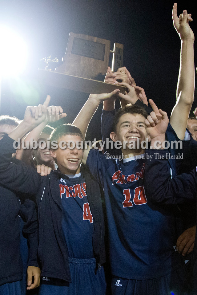 Heritage Hills' Ben Waninger and Carson Leibering held up the trophy after defeating Northeast Dubois during the Class 1A sectional championship game in Lincoln City on Saturday. Heritage Hills won 5-3. <br /> Sarah Shaw/The Herald