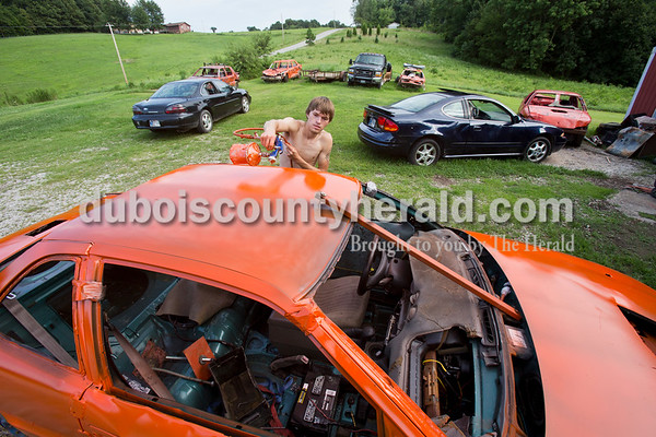 Shawn Ubelhor of Gentryville painted the demolition derby car of his cousin Justice Ubelhor orange using a paint sprayer at Justice's home in Ferdinand on July 22. The family paints their demolition derby cars orange and spray paints the names of loved ones in black.