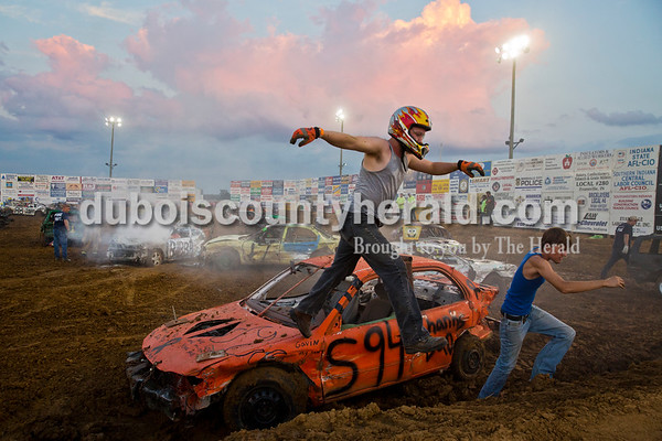 Joshua Songer of Dale, center, and Shawn Ubelhor of Gentryville exited Shawn's derby car as action was paused for firefighters to attend to the flames under the hood of the car driven by Shawn's uncle, Greg Ubelhor of Ferdinand, back left, during a demolition derby in Boonville on Sept. 4.