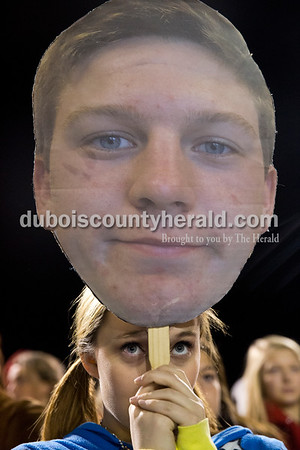 Heritage Hills senior Abby Hervey watched the game while holding a cardboard cut out of player Eddison Peters during Friday's 3A sectional football game in Lincoln City. Southridge defeated Heritage Hills 37-34 in double overtime. Sarah Ann Jump/The Herald