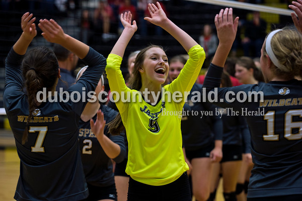 Jasper's Katey Bell, center, high-fived her teammates, Alexa Stenftenagel, left, and Riley Merder, right, after the first round of the Class 3A sectional against Princeton on Thursday night at Jasper High School. Jasper swept Princeton 25-19, 25-19, 25-16.    Alisha Jucevic/The Herald