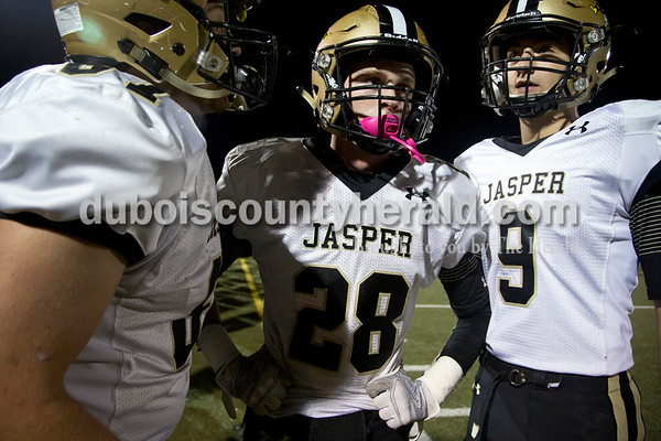 Jasper's Ian Jahn, left, Luke Lehane, and Jacob Lents talked on the sidelines during Friday's Class 4A sectional match against Evansville Harrison in Evansville. Evansville Harrison won 38-27.  Sarah Shaw/The Herald