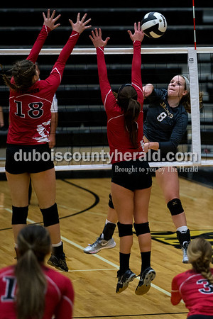 Jasper's Maria Gobert spiked the ball past Princeton's Mallory Smith, left, and Easton Chandler during the first round of the Class 3A sectional on Thursday night at Jasper High School. Jasper swept Princeton 25-19, 25-19, 25-16.    Alisha Jucevic/The Herald
