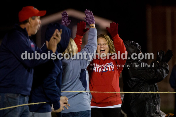 Heritage Hills fan Paula Carpenter of Santa Claus, center right, cheered and high-fived Jennifer Lashley of Lamar after Heritage Hills scored during Friday's 3A sectional football game in Lincoln City. Jennifer Lashley is the mother of player Grant Lashley. Southridge defeated Heritage Hills 37-34 in double overtime. Sarah Ann Jump/The Herald