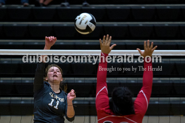Jasper's Jocelynn Morrow spiked the ball as Princeton's Kennedy Hardiman jumped to block during the first round of the Class 3A sectional on Thursday night at Jasper High School. Jasper swept Princeton 25-19, 25-19, 25-16.     Alisha Jucevic/The Herald
