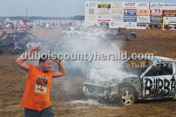 Greg Ubelhor of Ferdinand motioned that he was uninjured as he walked off the track following two fires in his car during the demolition derby in Boonville on Sept. 4.