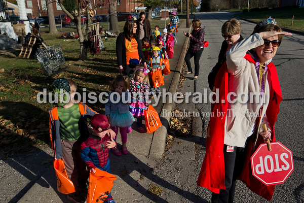 Holland Elementary preschool teacher Vicki Schulthise, right, showed the preschools how to look for oncoming traffic as they waited to cross the street to the local doctor and dentist office on Tuesday morning during their Halloween parade in Holland. The class also visited the local bank and a neighbor who use to assist at the school. After their parade to local stops next to the school, the students visited the  classrooms to show off their costumes and spread Halloween spirit.  Alisha Jucevic/The Herald