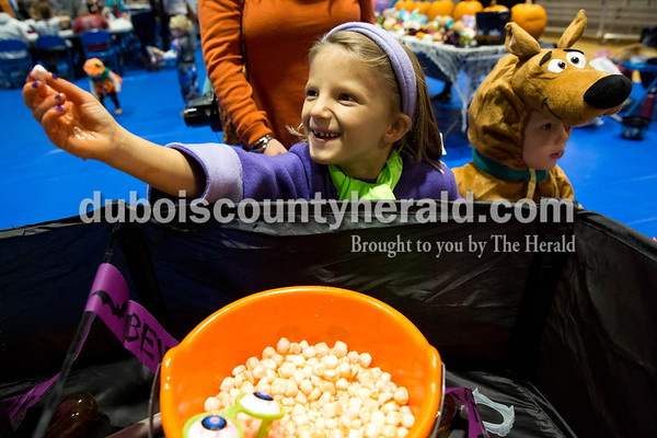 """Sarah Ann Jump/The Herald """"It's just a marshmallow,"""" exclaimed Mya Uebelhor of Ferdinand, 7, after squishing her hands in a bowl of """"eyeballs"""" during Fright Night at Vincennes University Jasper Campus on Friday. Her three-year-old brother Gavin, right, did not want to touch the mystery body parts. The Campus Activities Board invited the community to play Halloween games and visit the table decorating contest. Visitors voted for which table was their favorite."""