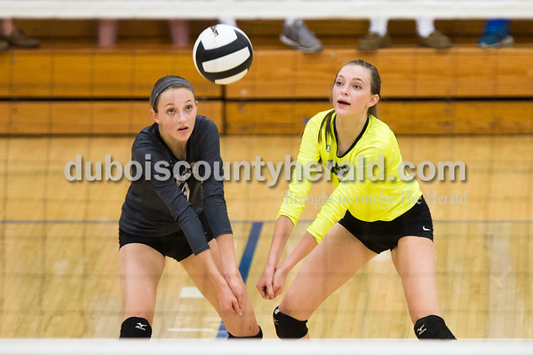 Jasper's Libby Bell, left, and Katey Bell leaned in to bump the ball during Tuesday's 3A regional championship volleyball match in Evansville. Evansville Memorial defeated Jasper in four sets. Sarah Ann Jump/The Herald