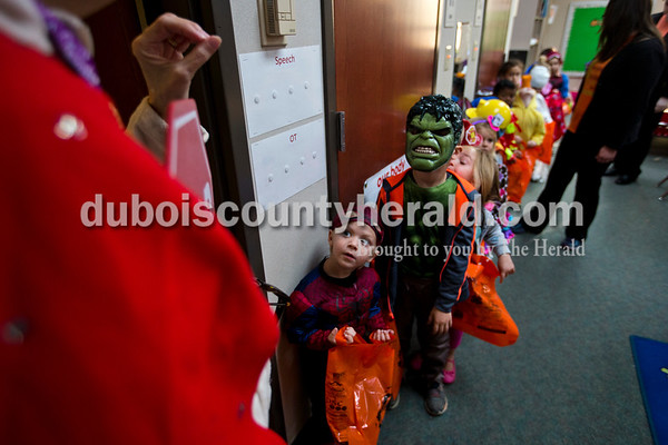 Eli Hildenbrand, center, and Henry Heile, right, looked up at their teacher Vicki Schulthise as she prepared the preschool class for their Halloween parade on Tuesday morning at Holland Elementary. The class paraded across the street to the local bank, a doctor's office, a dentist's office and a neighbor who use to assist at the school. The students also visited the other classrooms to show off their costumes and spread Halloween spirit.  Alisha Jucevic/The Herald