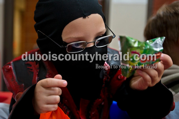Dressed as a ninja, Holland Elementary preschooler Tyler Wilz inspected a ring pop after the preschoolers returned from their Halloween parade on Tuesday morning in Holland.   Alisha Jucevic/The Herald