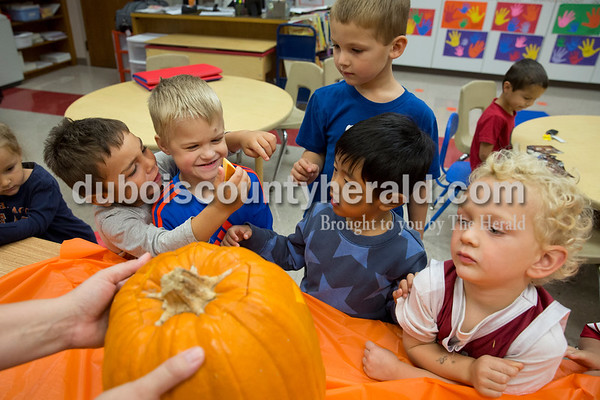 Sarah Ann Jump/The Herald Holy Trinity Catholic School Central Campus pre-schooler Zane Price, left, showed a piece of pumpkin to Henry Schmid as Caleb Hawkins and Edon Mu looked on, Braden Wehr checked out the carved pumpkin and Martin Loya, back right, looked at photographs from 1981 when Ron Mehringer visited his daughter Gina's kindergarten class to carve a pumpkin, at the school in Jasper on Monday afternoon. Ron Mehringer of Jasper continued the tradition by visiting his granddaughter Skylar Lee's pre-school class.