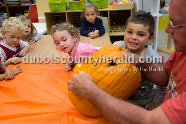 Sarah Ann Jump/The Herald Holy Trinity Catholic School Central Campus pre-schoolers Braden Wehr, left, Emilie Sternberg, Skylar Lee, Sophie Bower and Zane Price gathered around as Skylar's grandfather Ron Mehringer of Jasper carved a pumpkin at the school in Jasper on Monday afternoon