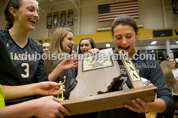 Jasper senior Alexa Stenftenagel bit the sectional championship trophy after the team's win over North Harrison in Saturday's 3A sectional championship volleyball match in Jasper. Jasper defeated North Harrison 3-1 for the title. Sarah Ann Jump/The Herald