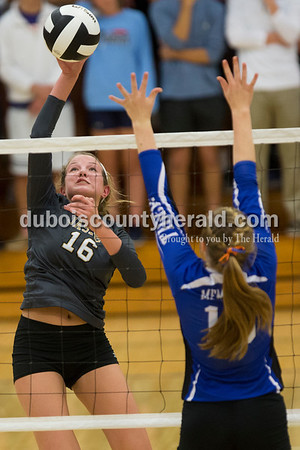 Jasper's Riley Merder spiked the ball over the net as Memorial's Abby Shafer defended during Tuesday's 3A regional championship volleyball match in Evansville. Evansville Memorial defeated Jasper in four sets. Sarah Ann Jump/The Herald