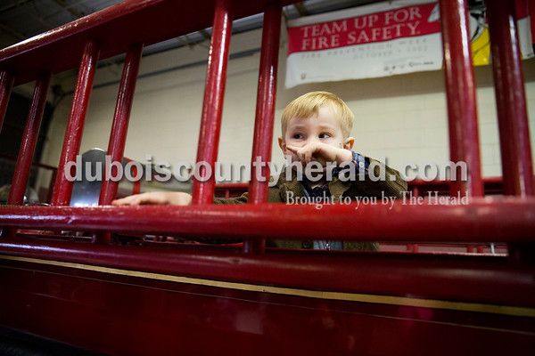 "Tristan Catt of Jasper, 2, looked around a 1929 fire engine while waiting to visit with Santa at the Jasper Fire Station on Friday. ""He loves firetrucks and big ladders,"" said his mother Traci Catt. Sarah Ann Jump/The Herald"