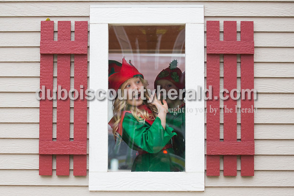 Andyn Lampert of Ireland, 8, left, waved as she spotted a friend from inside Santa's house where she was helping out as an elf with Lauren Mundy of Ireland, 8, right, during Santa's arrival in Jasper on Friday. Sarah Ann Jump/The Herald